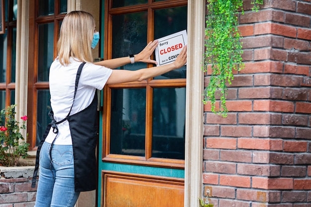 Caucasian waitress woman wearing medical mask puts sorry we're closed pandemic sign on cafe window