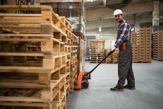 Кавказский складской рабочий поднимает вес с помощью ручного домкрата для поддонов