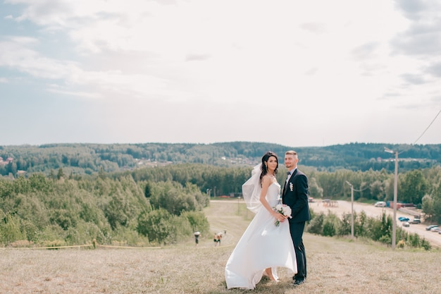 Caucasian wedding couple posing at top of mountain in sunny day