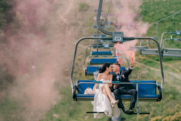白人の結婚式のカップルが手にカラフルな煙で索道に乗っています。