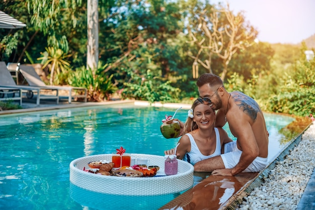 Caucasian wife and husband enjoy their holidays in thailand. joyful guy and girl laugh and swim in pool in luxurious hotel.