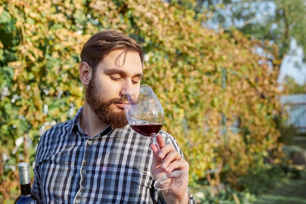 Caucasian wine maker drinking glass red wine, tasting it checking quality standing in vineyards