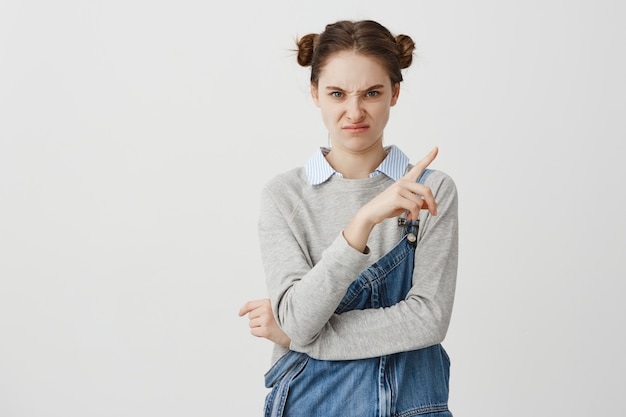 Caucasian woman 20s showing finger over white wall twisting her face. adult girl with childish hairstyle expressing dislike and aversion. copy space