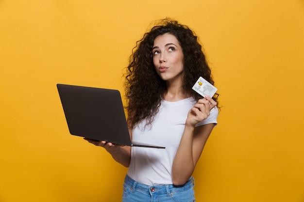 Кавказская женщина 20-х годов в повседневной одежде держит черный ноутбук и кредитную карту, изолированную на желтом