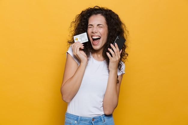 Кавказская женщина 20-х годов в повседневной одежде держит мобильный телефон и кредитную карту, изолированную на желтом