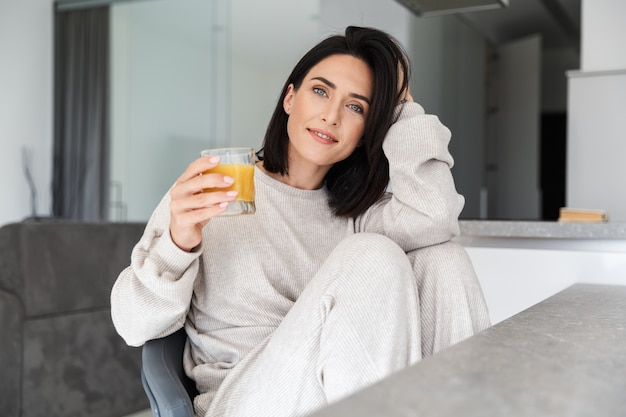 Caucasian woman 30s drinking orange juice, while resting in bright modern house