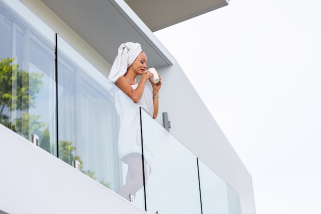 수건으로 샤워 한 후 백인 여자는 빌라의 발코니에 서서 커피 또는 차를 마시고 하루의 완벽한 시작 진정 편안한 여성이 새로운 하루를 만납니다.