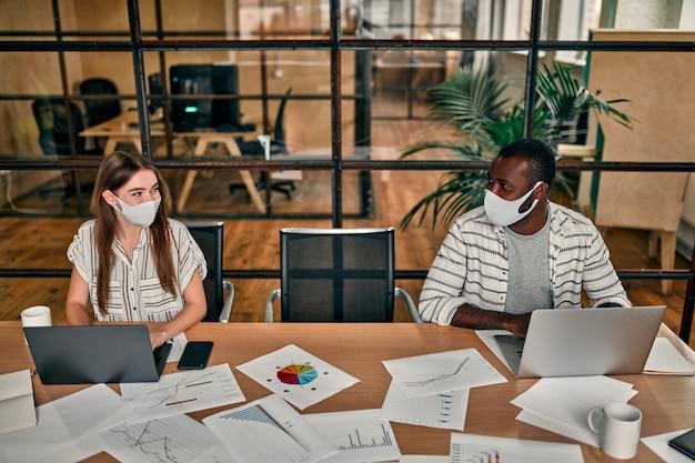백인 여자와 아프리카 계 미국인 남자 보호 마스크를 쓰고 그들의 거리를 유지, 현대 사무실에서 랩톱에서 작동합니다.