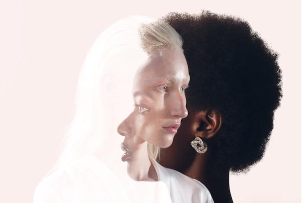 黒の背景に白人女性とアフリカ系アメリカ人女性の肖像画。女性の友情、愛と関係の概念。