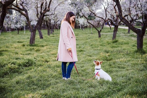 백인 여자와 석양 봄 날에 공원에서 개. 사랑과 우정 개념. 야외에서 애완 동물