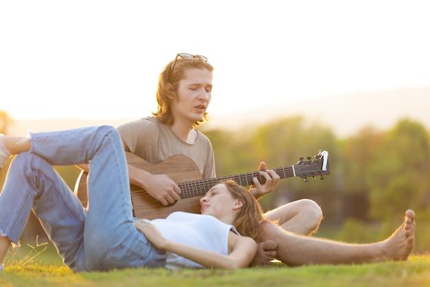 Кавказская женщина и красивый мужчина проводят время вместе в кемпинге на природе и играют на гитаре.