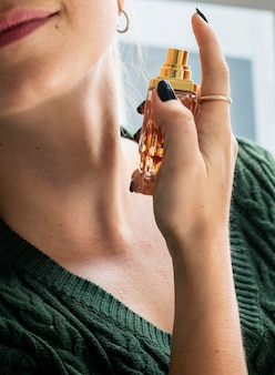 Caucasian woman applying perfume to her neck