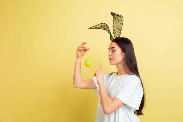 黄色のスタジオの背景にイースターバニーとして白人女性。