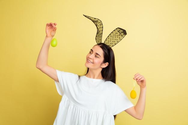 Donna caucasica come un coniglietto di pasqua su sfondo giallo studio. auguri di buona pasqua.