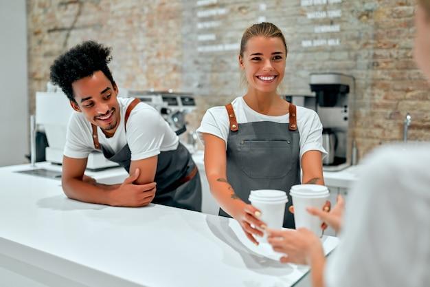 커피 숍에서 고객에게 커피, 라떼 또는 카푸치노 컵을주는 백인 여자 바리 스타.