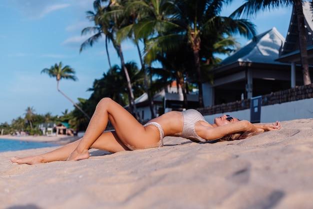 Donna caucasica in bikini e occhiali da sole sulla spiaggia tropicale