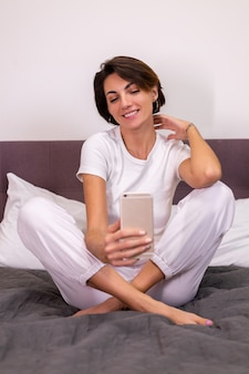 Caucasian woman blogger at home in casual clothes cozy bedroom take photo selfie on mobile phone in mirror