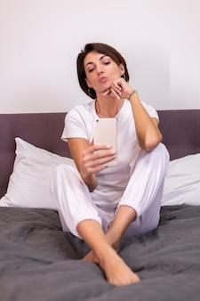 La donna caucasica blogger a casa in abiti casual accogliente camera da letto scatta foto selfie sul cellulare in specchio