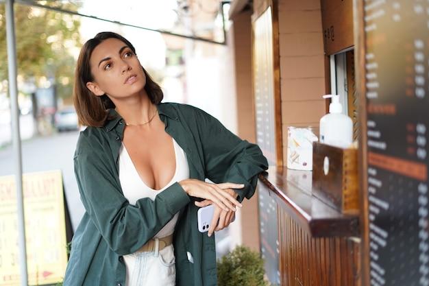 コーヒースポットでコーヒーを買う白人女性、思慮深く考えて選択する屋外の窓の日没時間