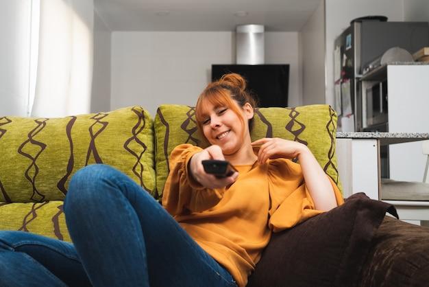 Кавказская женщина переключает канал с помощью пульта дистанционного управления, сидя на диване у себя дома
