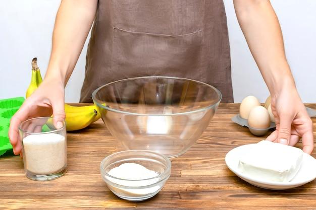 코티지 치즈 바나나 머핀 컵케익 캐서롤을 만들기 위한 재료를 준비하는 앞치마를 입은 백인 여성 요리사, 온라인 요리, 조리법 지침