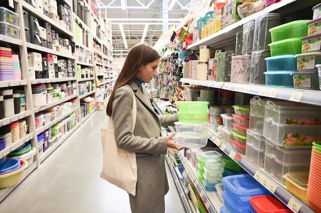 Кавказская женщина выбирает контейнер для еды в супермаркете.