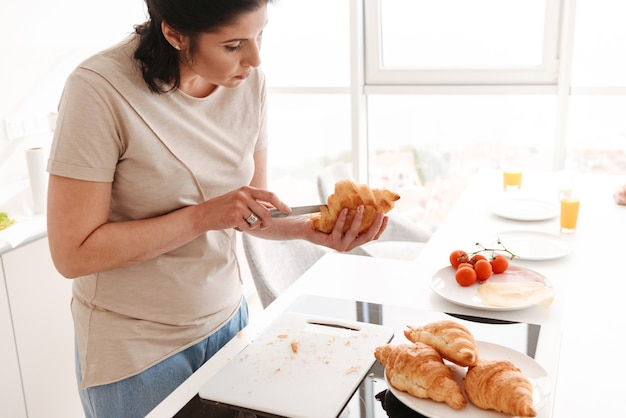 Caucasian woman cooking breakfast for her family in home kitchen, with cutting croissants