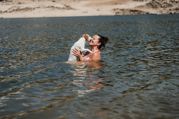 Caucasian woman and cute jack russell dog swimming in lake and having fun together. vacation and relax concept