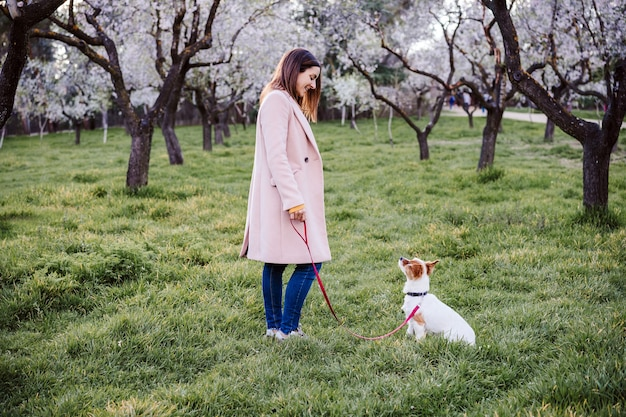 Caucasian woman and dog in park in springtime at sunset. love and friendship concept. pets outdoors