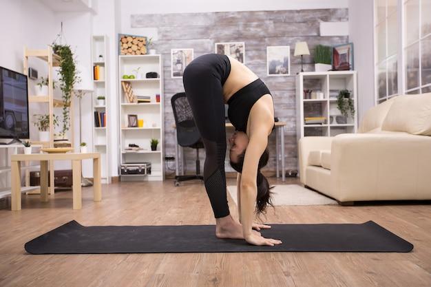 Donna caucasica che fa posa di flessibilità di yoga sulla stuoia in soggiorno. stile di vita pacifico.