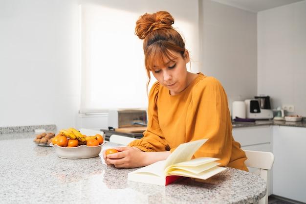 Кавказская женщина, одетая в желтое, читает книгу на столе на своей кухне