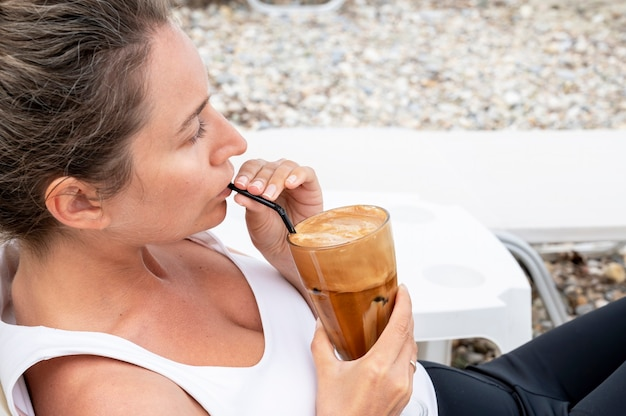 La donna caucasica che beve la bevanda del caffè su una spiaggia con schiuma e cannuccia