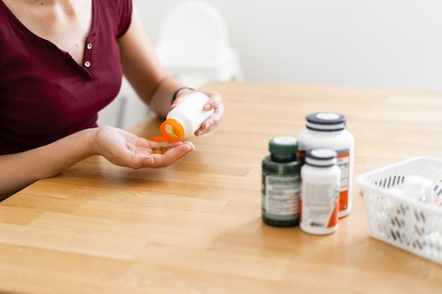 Кавказская женщина пьет много таблеток. профилактическая медицина. пищевые добавки