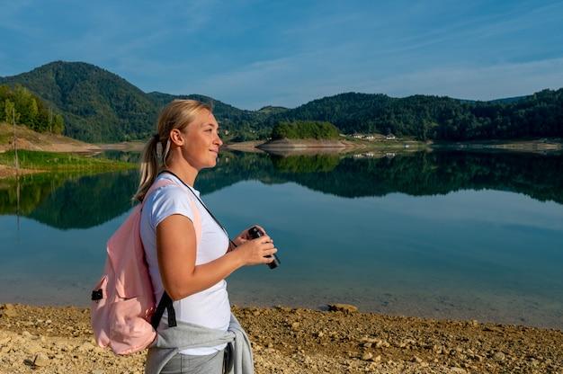 Кавказская женщина, наслаждаясь видом в бинокль, стоя возле красивого спокойного озера