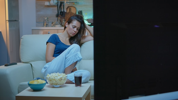 Caucasian woman falling asleep on sofa at home while watching tv. tired exhausted lonely sleepy housewife in pajamas sleeping in front of television sitting on cozy couch in living room.