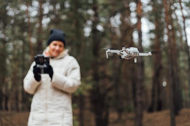 秋の森で空中ドローンを飛んでいる白人女性。