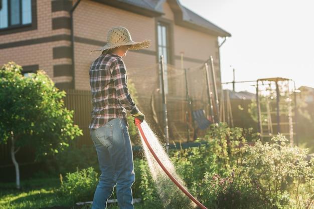 晴れた暖かい夏の日に彼女の菜園のベッドに水をまく作業服を着た白人女性の庭師。庭とあなたの農場で働くことの概念
