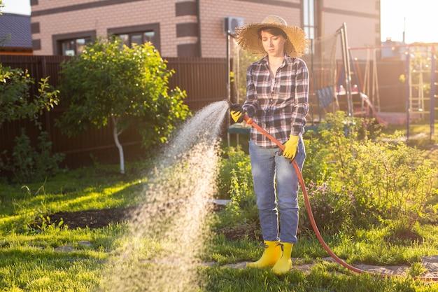 日当たりの良い暖かい日に彼女の菜園のベッドに水をまく作業服を着た白人女性の庭師