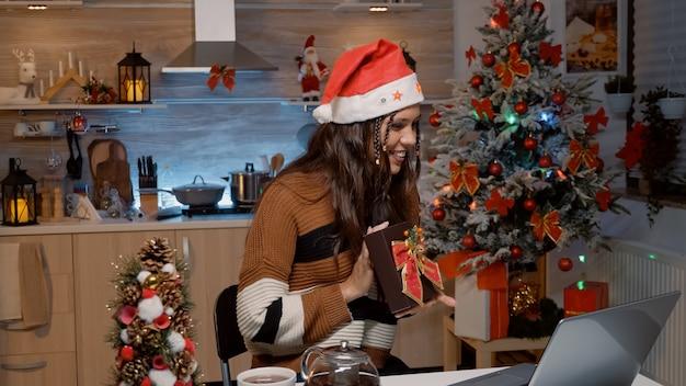 ビデオ通話技術で贈り物をする白人女性