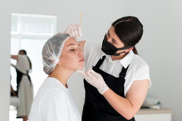 Caucasian woman going through a microblading procedure