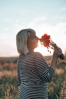 Кавказская женщина рука букет цветов мака на фоне луга на закате