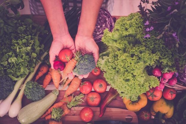 白人女性の手は、準備して調理する準備ができているいくつかの新鮮な野菜を取ります