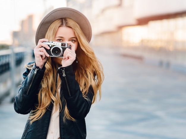 Caucasian woman in hat using camera outdoors