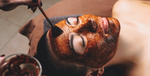 Caucasian woman having a facial care treatment with a cacao mask applied at the spa salon