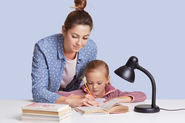 Caucasian woman helping her doughter to do school homework, mother and child surronded by books, little girl sitting concentrated at white desk, trying to do sums. education concept.
