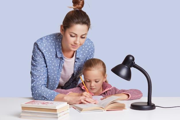 白人の女性が娘に学校の宿題をするのを手伝い、母と子が本に囲まれ、座っている少女は白い机に集中して、合計を計算しようとしました。教育のコンセプトです。