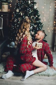 La donna caucasica e suo marito si rilassa insieme nel soggiorno nell'atmosfera natalizia.