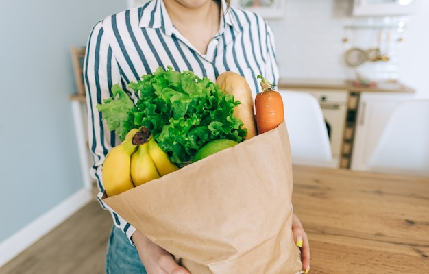 Caucasian woman hold eco shopping bag with fresh vegetables and baguette in modern kitchen at home.