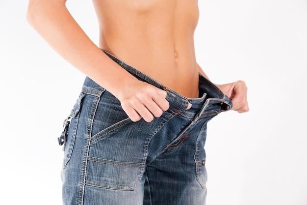 Кавказская женщина держит свои старые джинсы, чтобы показать похудение