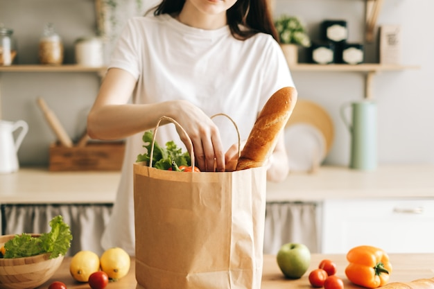 Caucasian woman hold shopping bag with fresh vegetables in kitchen
